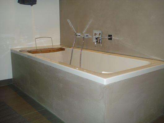 Weiße Corian-Badewanne mit grau-braunem Marmorputz ...