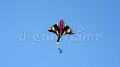 An isolated colorful kite flying in the clear blue sky in a hot summer day.