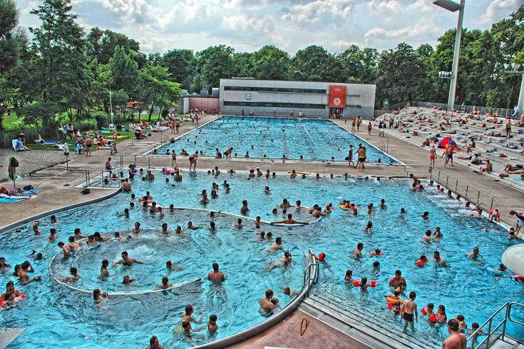 """Nirgendwo sonst in München gibt es mehr Schwimmbecken in einem Freibad als hier im """"Dante"""". Natürlich stehen auch im Sommer das 50-m-Stadionbecken (ca. 27° C) und das Erlebnisbecken (ca. 30° C) mit Massagedüsen und Strömungskanal zur Verfügung. Besonders beliebt bei Sonnenanbetern: die Tribüne des Stadions mit rund 1000 Plätzen.   Auch den jüngsten Badegästen garantiert das Dante-Freibad einen tollen Badetag. Ein kleineres Nichtschwimmerbecken mit Rutschen und ein Kinderspielplatz laden zum…"""