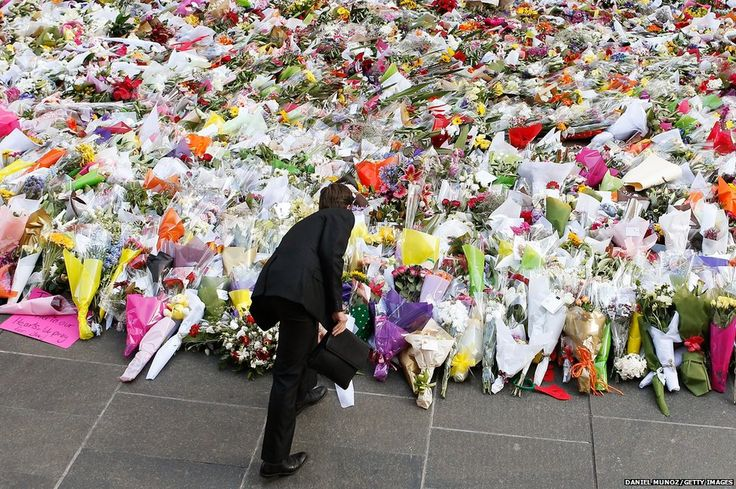 A man places flowers as a mark of respect for the victims of Martin Place siege in Sydney, Australia 12.16.14