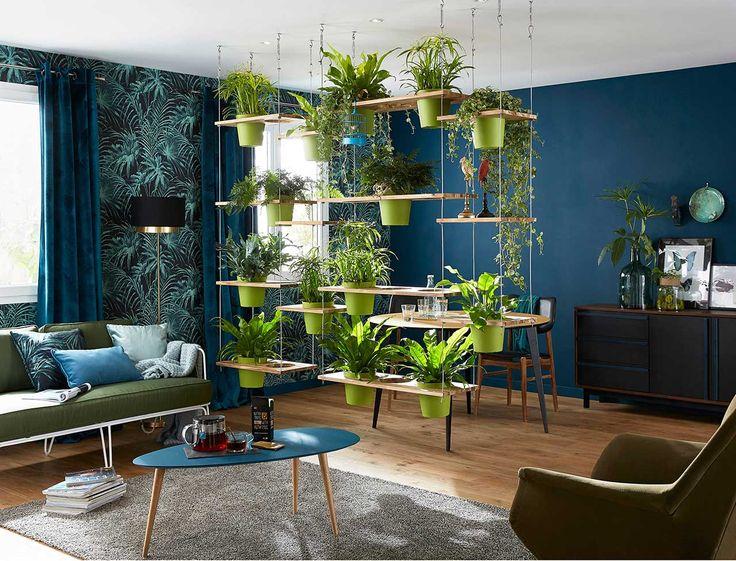 Un mur végétal en guise de cloison, des couleurs chic et intenses, du mobilier aux accents fifties, côté déco ce salon a tout bon ! Equipé d'un mobilier rétro habillé de teintes intenses, ce salon-salle à manger élégant joue la fantaisie avec sa cloison végétale suspendue. Des couleurs tendance et intenses. Vert greenary, bleu canard ou celadon, turquoise, une palette complète de teintes est ici déclinée pour apporter du relief au décor. Ce mélange tropical et animé éclaire les tons sourd...