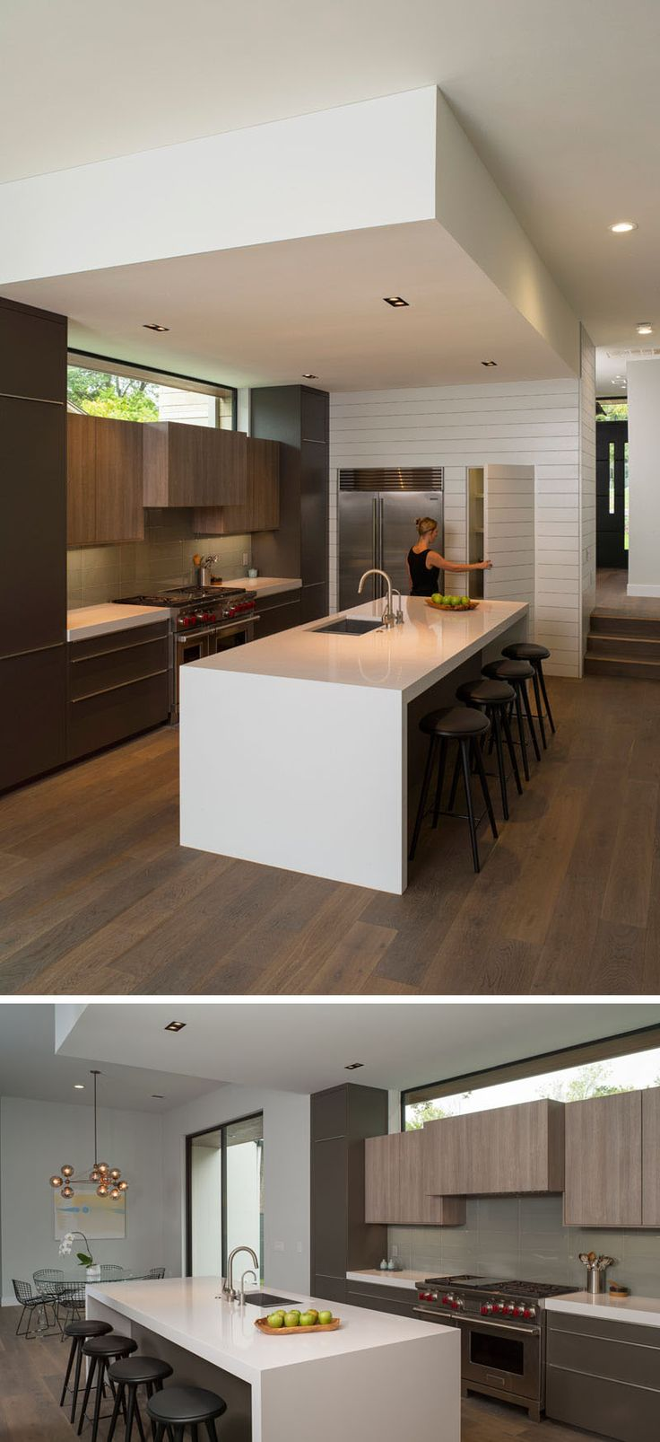 In this modern kitchen, the large white island with seating has plenty of room for guests to sit and chat, and a pantry is hidden sits beside the fridge.