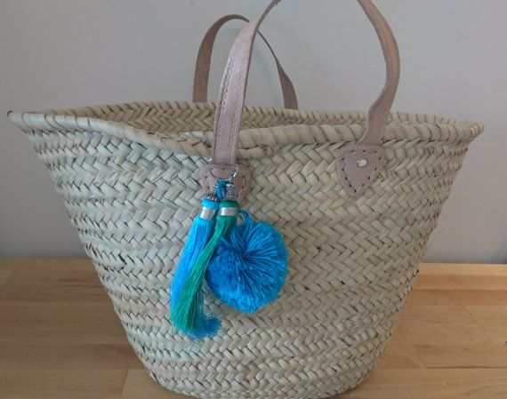 A gorgeous Moroccan handmade basket with soft leather handles, perfect for the beach, picnics, shopping or about town accessorised with lovely moroccan style tassels and a pom pom. (removable)  Mermaid option: blue pompom with blue and green tassels Fire& Earth option: red pom pom with gold and orange tassels Sophisticated grey option: 1 large grey tassel Natural option: Gold and orange tassels  These bags measure aprox 50cm across the top and 30cm in height at the tallest point. Due to t...