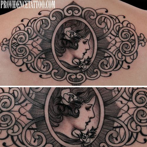 Curlicue frame around a broochlike vintage style side portrait. Done by Dennis M. Del Prete at Providence Tattoo.