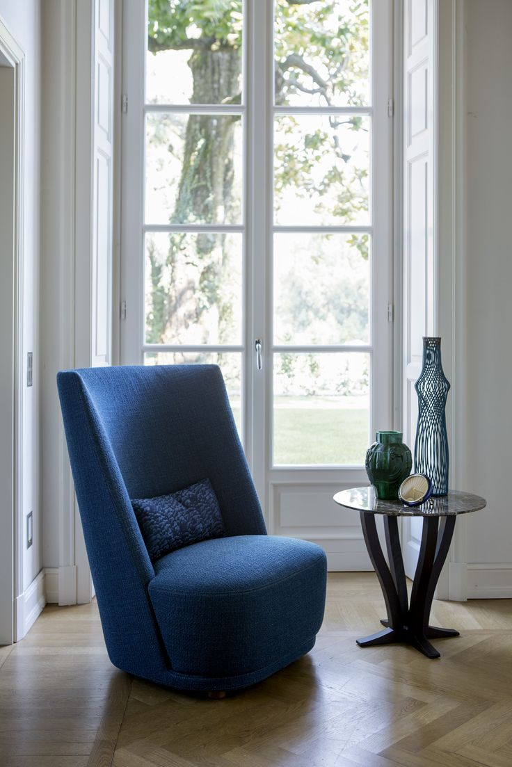 VIVIEN high armchair and ELIZABETH small round table The high armchair VIVIEN fascinating for its sleek and sinuous shape; it gives a touch of class to public and private spaces. Fabric and leather covers.