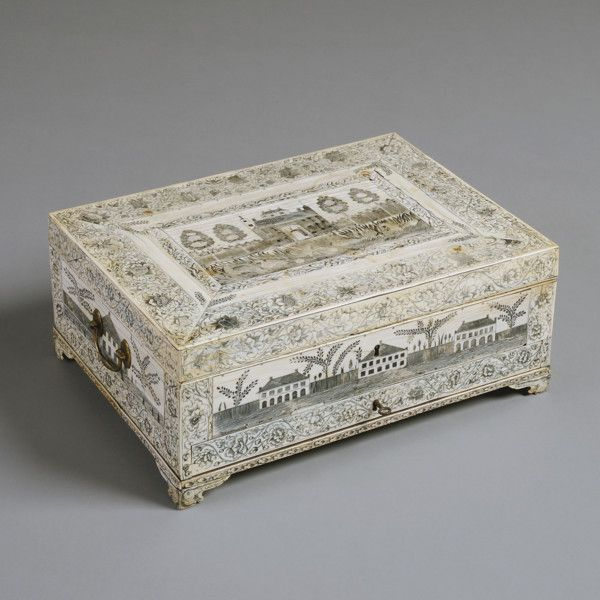 A FINE ANGLO-INDIAN ENGRAVED IVORY WRITING BOX, VIZAGAPATAM, CIRCA 1775.  Engraved with architectural scenes within foliate scroll borders, the bracket feet engraved with elephant heads. The interior fitted with hinged writing slope, inkwells and compartments and containing the original weighted ivory presse papiers.