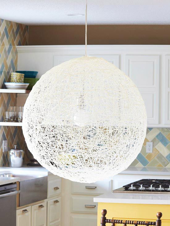 Create a chic, midcentury pendant fixture using just string and a balloon. Purchase a 35-inch balloon from a party goods store, and blow it up to about 30 inches. Brush it with a thick coat of fabric stiffener, which you can find at fabrics and crafts stores. Wrap the balloon with white crochet string, brushing on more stiffener as you work to ensure a thick coating. Let dry for 24 hours, then pop the balloon. DIY Steps: Illuminate the shade using an inexpensive light kit for hanging…