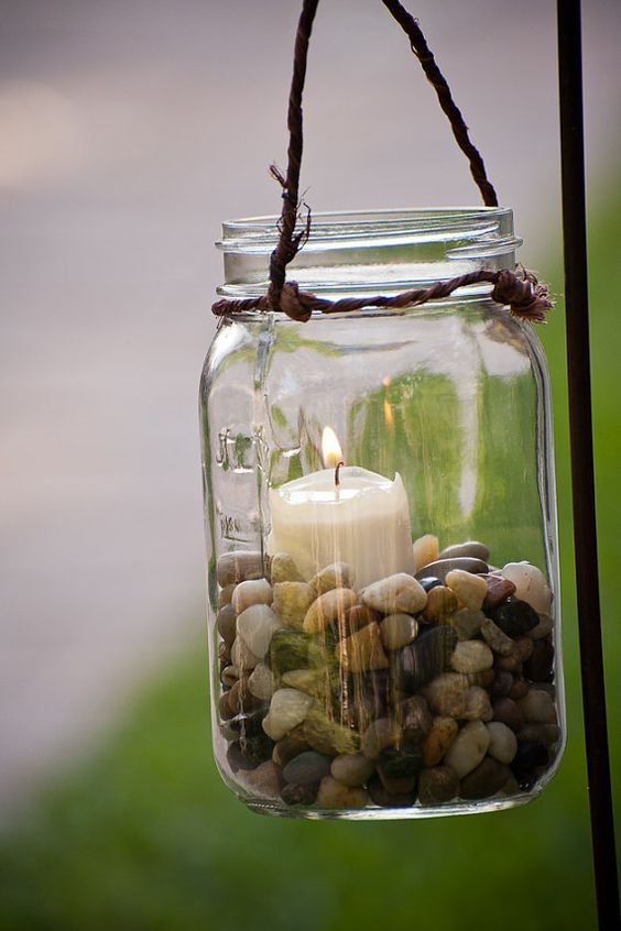 "Mason jar hanging candle holders.  Use sand instead of pebbles.  Some jars can be coated with glass paint to match colored bottles.  12 quart size jars are about 11.00.  Suggest different sizes.  Small jelly jars are ""quilted"" creating a faceted glow from candle.:"