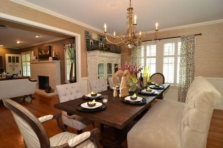 The dining room branches out with a large, tufted bench that serves as seating at the table. An elegant chandelier, distressed China cabinet and printed curtains add a softness to the space.