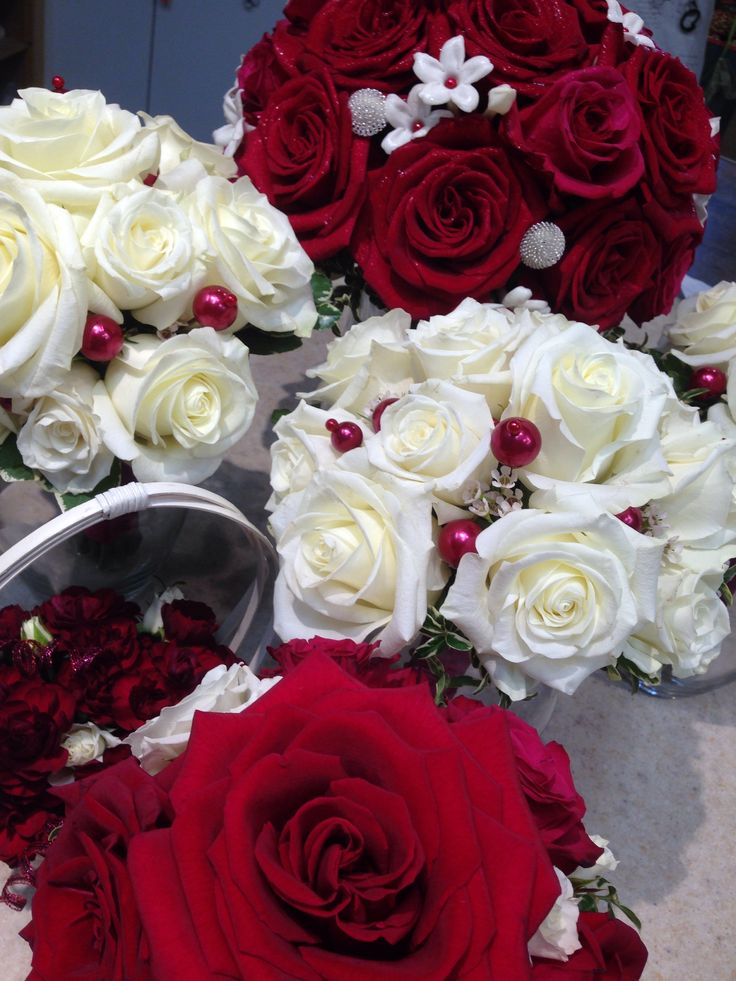 Christmas wedding bells! The classic elegance of red and white roses in these bridal bouquets blend with the sweetness of the flower girl's basket to produce the warmth and emotion anticipated in this time of year.