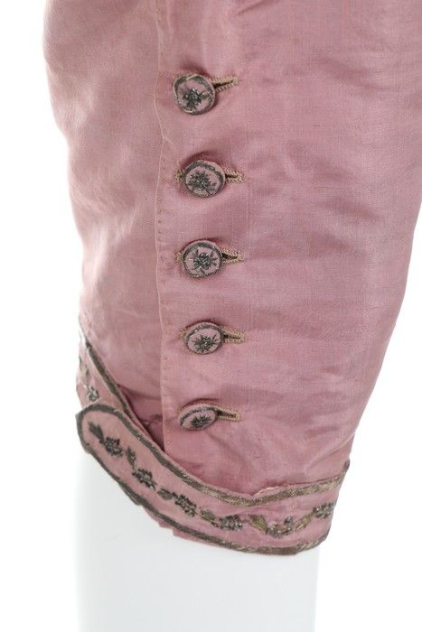 Detail buttons, pair of breeches, late 18th century. Lilac silk taffeta with silver thread embroidered knee buttons and band.