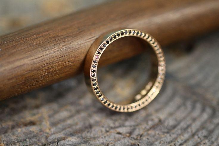 Keltakultaisessa sormuksessa mustat timantit sekä yksi pinkki safiiri istutettuna hauskasti sormuksen sivuun. CaiSanni.