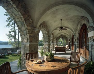 The vaulted ceiling of this portico with stone arches is as beautiful as the view of the water and hills. A dining table and chairs with comfortable seat cushions allow for leisurely meals. The far end has a seating area. Wall sconces provide attractive lighting, while ceiling fans keep a breeze going during the heat of the day.