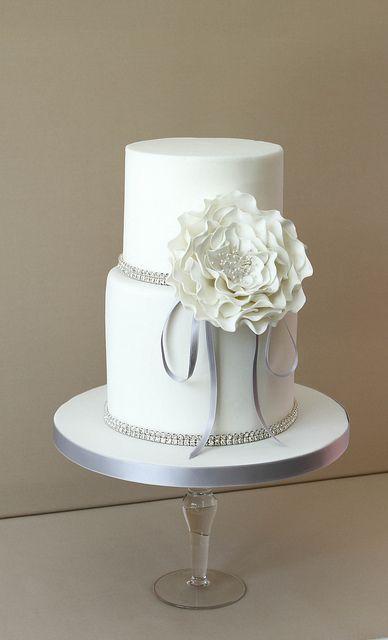 Torta de boda de dos niveles color blanco decorada con cinta de imitación de diamantes y flores de azúcar, muy vintage. #BodasVintage