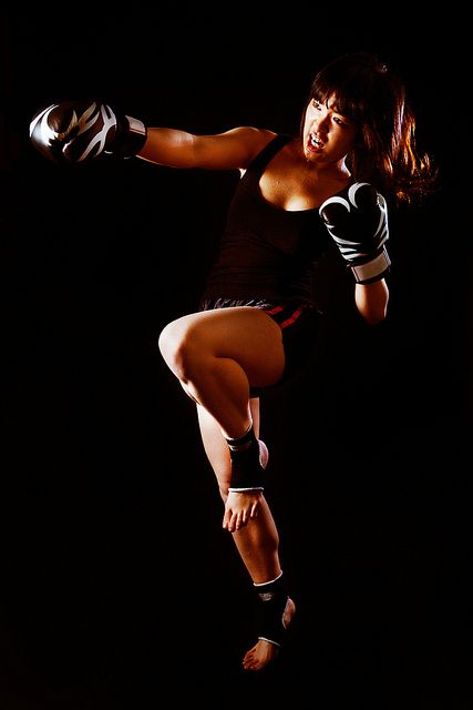 | Young Asian Woman Muay Thai fighter in defensive position