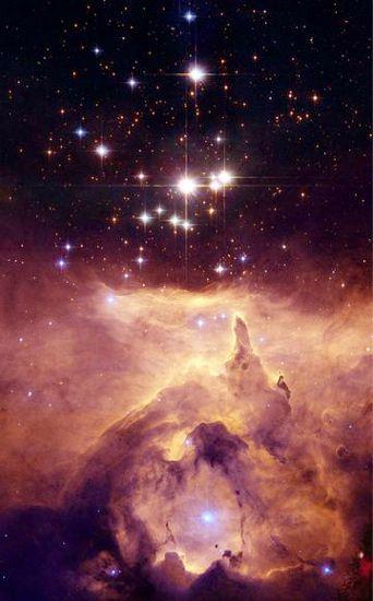 """L'ammasso stellare Prismis 24 appare sospeso sopra la gigantesca nebulosa NGC 6357 in una foto di Hubble del 2006. All'interno della nebulosa, situata nella costellazione dello Scorpione, a 8.000 anni luce da noi, sono nascoste centinaia di stelle massicce centinaia di volte più grandi del Sole, che riscaldano il gas che circonda l'ammasso creando la """"bolla"""" cavernosa visibile in basso nell'immagine."""