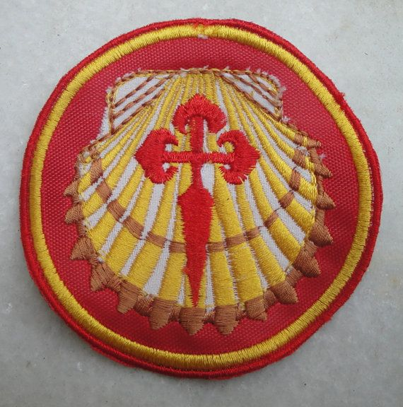 scallop shell with the cross of St james on a pilgrim patch for Camino de Santiago.