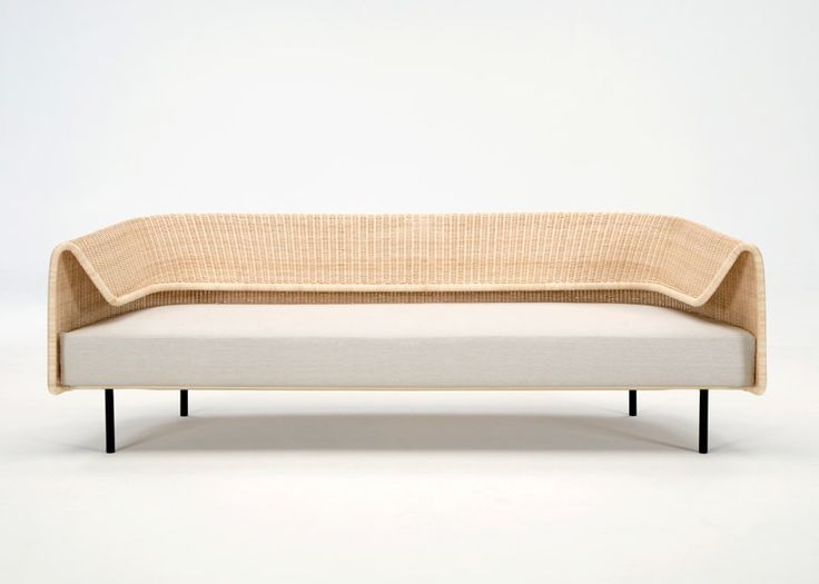A curved rattan structure forms the flexible backrest of this sofa.