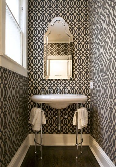 Love how the white sink and white towels pop off of the pattern black and white wallpaper.   Even the baseboard calms the paper down!