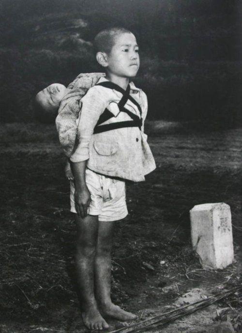 """Alguns não são abençoados com vidas fáceis. """"Órfão japonês estóica, em posição de sentido ter trazido seu irmão morto mais jovem para uma pira de cremação, Nagasaki, pelo fotógrafo americano, Joe O'Donnell 1945."""""""