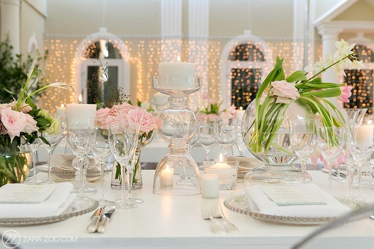 Romantic wedding reception table decor with white rectangular tables, glass vases, tulips and soft pink roses.