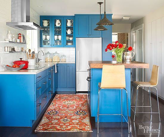 Nixing the peninsulain favor of a slim island proved to be a game-changing choice. Blue cabinetry contrasts with dark hickory floors, while brushed-metal drawer pulls give a nod to the room's underlying rustic aesthetic.