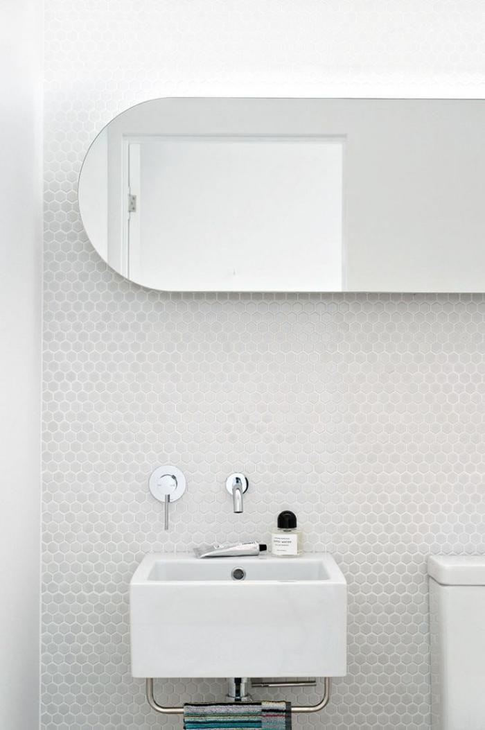 carrelage blanc brillant, lavabo suspendu au mur blanc
