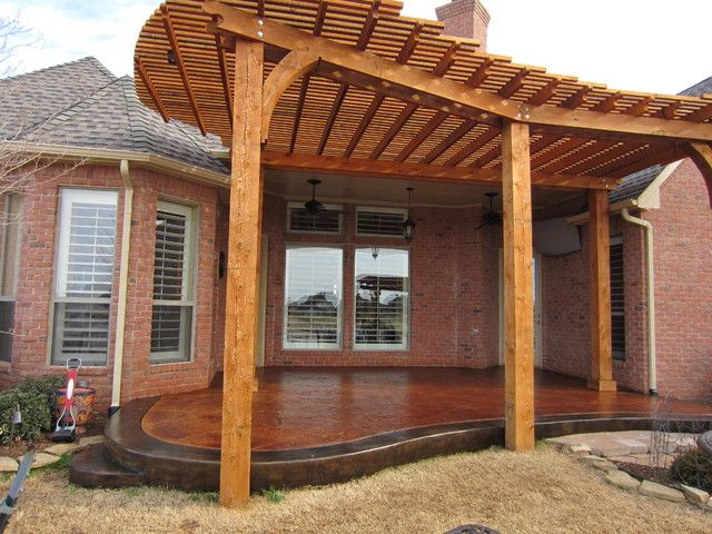 A custom pergola overhanging a stained concrete patio.
