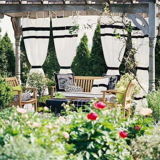 Give any pergola a makeover with a set of curtains. Here, a black-and-white color scheme blends well with the faded silvery-gray patina of the wood. The outdoor-friendly fabric is easy care, too./
