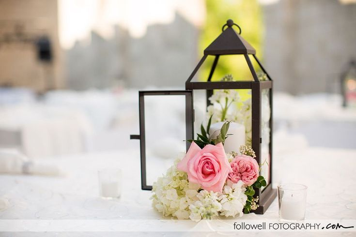 "Centerpiece #1 -  for 7 48"" round tables- Silver lantern with flower arrangement of white hydrangea, white stock, pink rose, hot pink ranunculus, greenery and a 6"" white pillar candle, surrounded by a mix of mercury glass and crystal votive candles and scattered crystals."