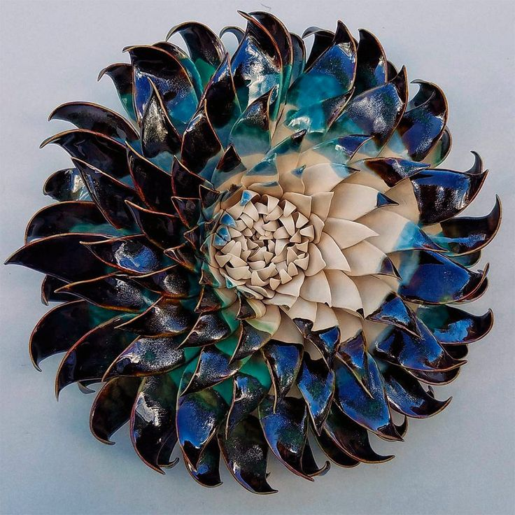 Художник - самоучка Оуэн Манн делает керамические цветы из десятков, а иногда и сотни лепестков, и это пышные пионы, буйные георгины, и жесткие спиралевидные суккуленты. В холодных оттенках синего и зеленого, фарфоровые цветы выглядят так, как будто они только что сорваны в саду, а не вышли из мастерского скульптора.