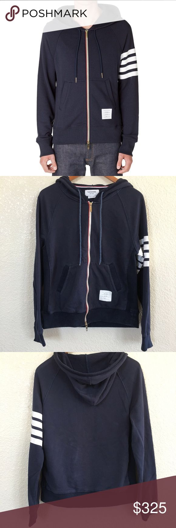 Thom Browne Full Zip Hoodie- Classic 4 Bar Stripes Regular Price $735. Navy 100% cotton full zip hoodie with classic four bar stripes. Gold zipper.Red white and blue grosgrain ribbon detailing. Kangaroo pockets. 3 inch side ribbing. Drawstring for hoodie (faded). Laundry tag size 3. No staining. No snags. Slight distressing around collar. Underarm to underarm: 20.5 inches. Length: 24 inches. Sleeve length: 19 inches. Thom Browne Sweaters Zip Up