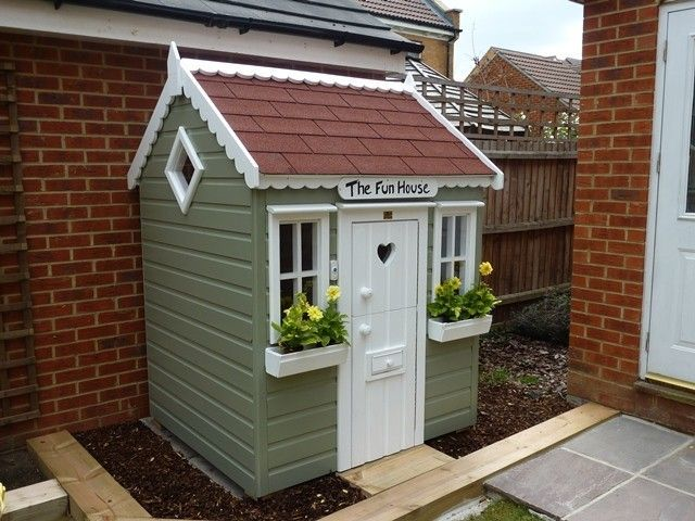 wooden playhouse with felt shingle roof & window boxes