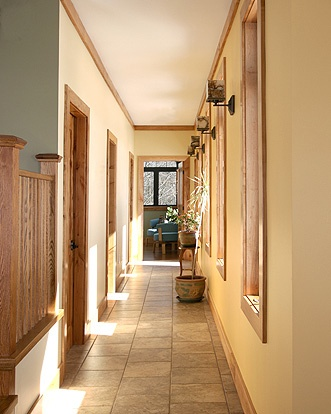 The Bootsma Residence - The corridor that leads to the guest bedrooms and bathroom is flooded with winter sun.  In the summer deep roof overhangs shade the south facade keeping the house cool and comfortable.