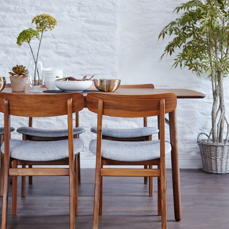 Inspired by mid-century modern design our Jersey Walnut Table will set a tone of style and substance in your home. This solid wood table has accent curved edges and refreshing grey upholstery for a comfortable dining experience.