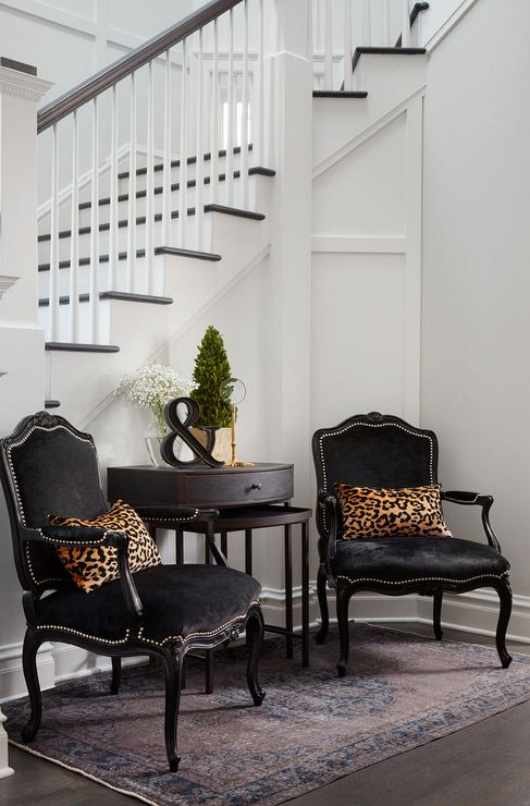 SuzAnn Kletzien - Chic foyer features a pair of black velvet French chairs accented with silver nailhead trim lined with leopard pillows flanking wood nesting tables. #Foyers