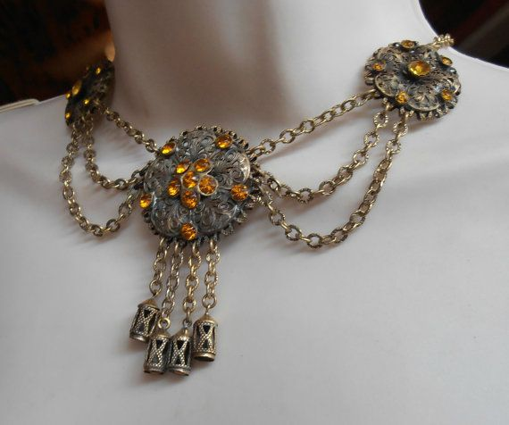 A stunning vintage Victorian Czech festoon bib necklace, featuring golden topaz colored paste rhinestones set into gilt brass filigree & featuring 4 dangling tassels. Wearable length is 16.5 and bib measures about 3 long, from the top of the center station, to the bottom of the dangling tassels.  The festoon bib necklace is in excellent antique condition, with no missing or replaced stones...a bit of age appropriate darkening here and there. Perfect for gift giving or as an addition to your…