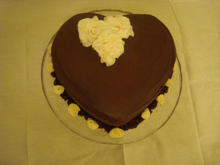 Torta al cioccolato e mandorle farcita con mousse ai frutti di bosco e ricoperta con ganache al cioccolato. fiori in pasta di zucchero