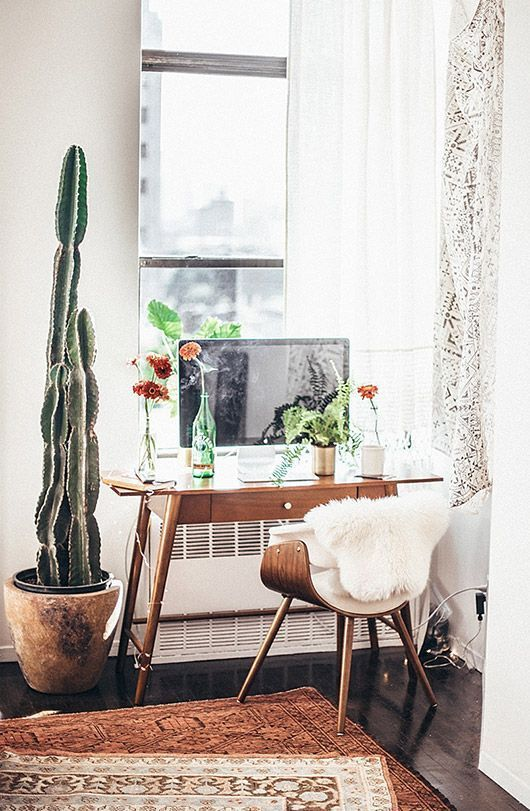 modern desk chair with faux fur and small wooden desk with tall potted cacti her