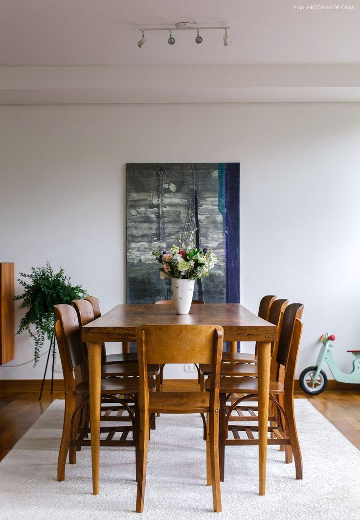 Sala de jantar tem mesa e cadeiras de madeira e tapete claro.