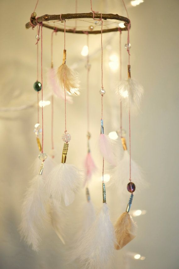 This is so soft and subtle, with its white, cream, and pink feathers. It features pink string and gold, silver and copper accents. It has crystal