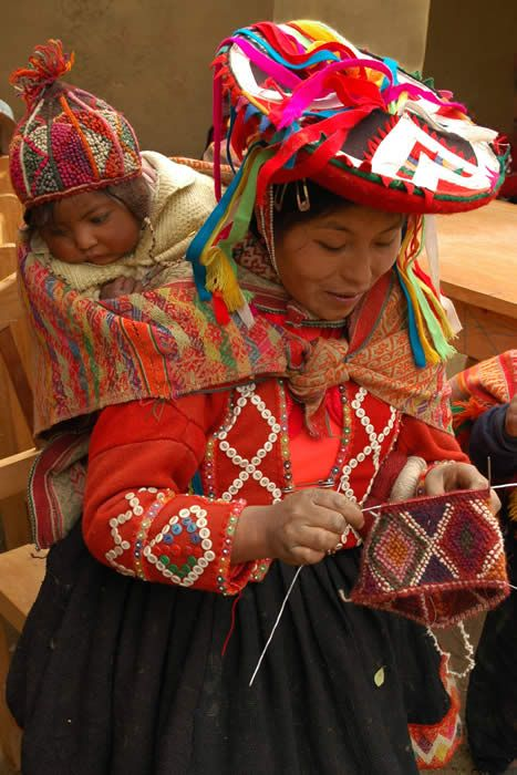 Mother Andean knitter and knitting with baby on back, wearing chullo hand-knit cap ~ Peru