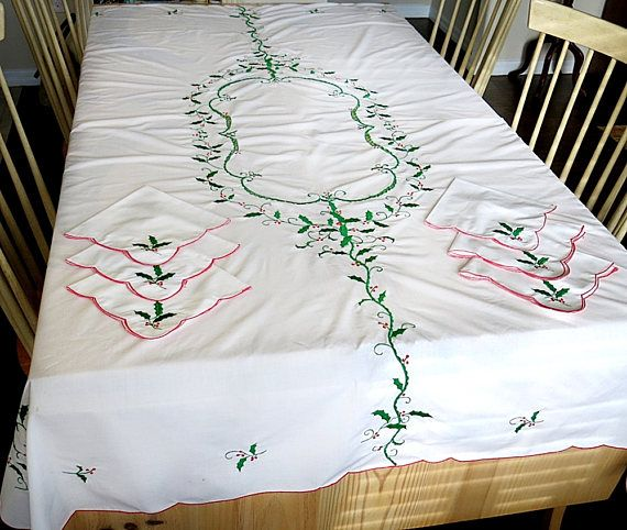 Here is a Christmas tablecloth and napkins set with a machine embroidered holly leave motif. There are twelve matching napkins with the rectangular tablecloth. The fabric is probably a cotton poly blend. The tablecloth and napkins both have a scalloped edge. The set is in very good vintage condition with some light spots and discolorations. The napkins look like they have not been used.  The holiday tablecloth measures 67 inches by 82 inches. The napkins are 16 1/2 inches square. This is...