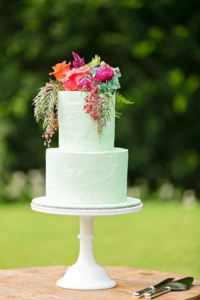 Photo: Calli B; a mint colored wedding cake with a bursting floral topper in hot fuchsia