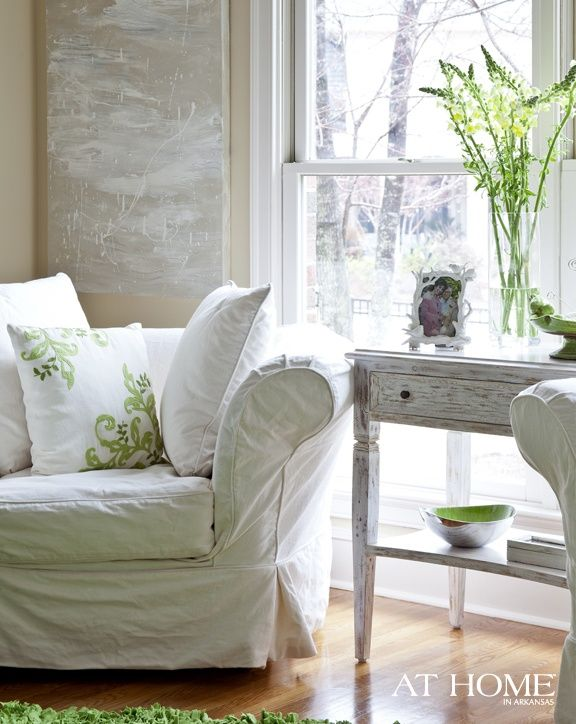 oversized white slip covered chair in white room with green accents