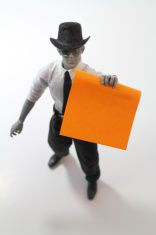 Plastic man holding blank orange note stock photo