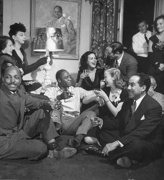 """I am a bit obsessed with this awesome picture. It's Hilda Simms, Langston Hughes (bottom right) and actor Canada Lee (center in white shirt) at a party with other artists around 1944."" - Vintage Black Glamour. Photo by George Karger/Pix Inc./Time Life Pictures/Getty Images."