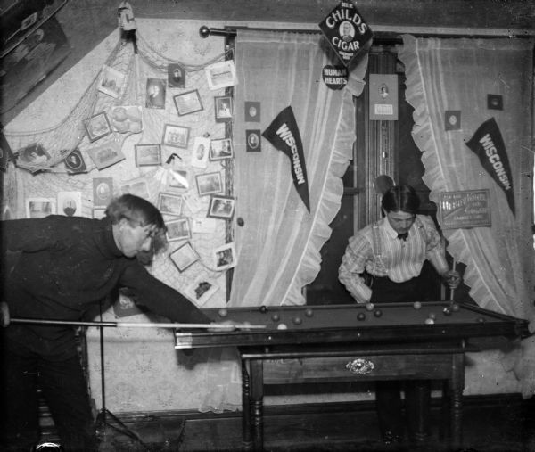 PLAYING POOL: Forest Middleton, left, prepares a pool shot while his opponent looks on. They are playing on a portable pool table in Forest's room. Photographs, cigar advertisements, and two Wisconsin pennants decorate the room.