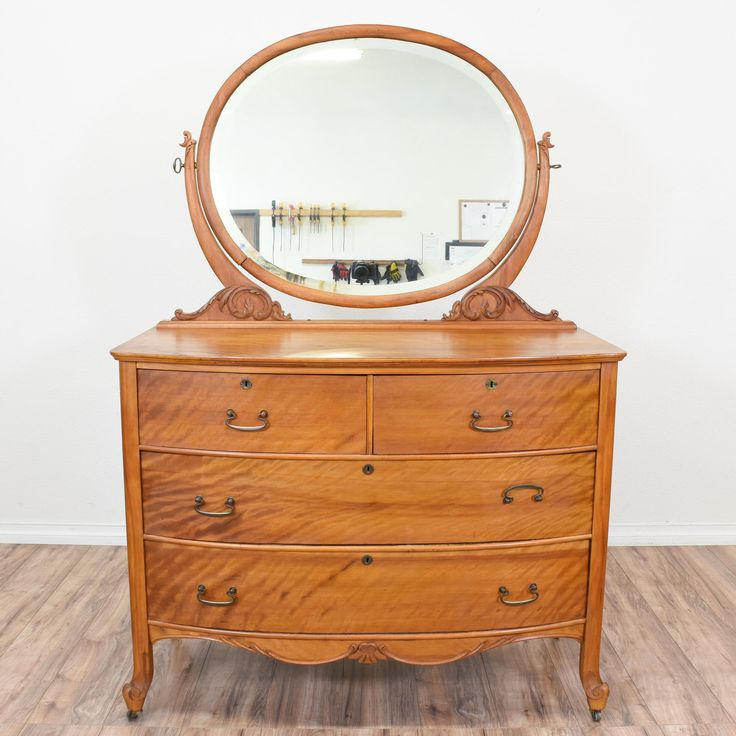 This victorian dresser vanity is featured in a solid wood with a gorgeous glossy tiger maple finish. This dresser is in great condition with a curved front, a round carved swivel mirror and 4 large drawers. Eye catching storage vanity with a rolling wheel base! #victorian #dressers #vanitydresser #sandiegovintage #vintagefurniture