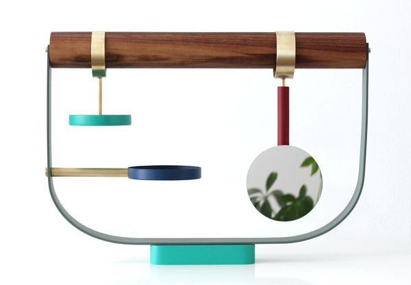 The Arbor Jewelry Stand is a colorful refuge for valued treasures. Its inspiration comes from bowerbirds, a unique bird species that collects and displays an array of brightly colored objects in and around its nest. The sculptural perch incorporates an integrated and removable mirror, brushed brass details, and colored platforms that display special items while keeping them safe. A detachable solid wood dowel acts as the main support for hanging necklaces, bracelets and other treasures